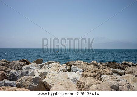 Rocks Against The Green Ocean At Malagueta Beach In Malaga, Spain, Europe With Clear Sky