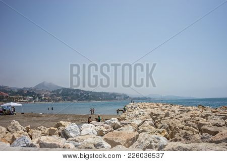 View Of The Ocean At Malagueta Beach With Rocks At Malaga, Spain, Europe On A Clear Sky Morning