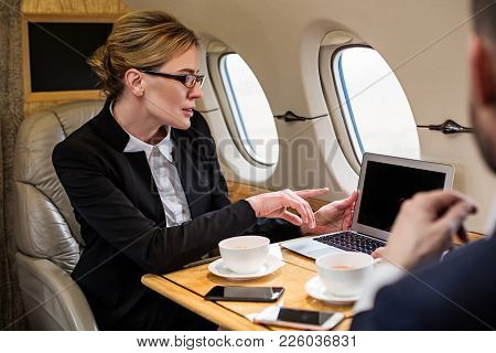 Good Looking Lady In Formal Clothes Discussing Work Matters With Her Companion While Sitting In Airp