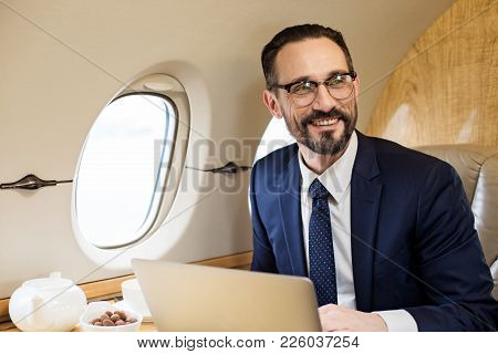 Portrait Of Neat Man In Suite Sitting In Airplane Seat With Laptop, He Is Looking Aside And Laughing