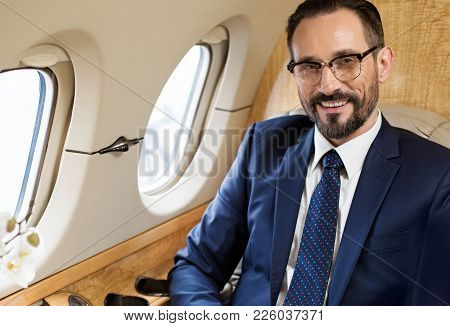 Waist Up Portrait Of Positive Imposing Businessman In Airplane Sitting In His Seat And Smiling