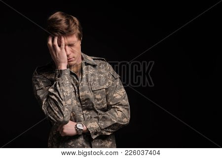 Cheerless Male Veteran Holding His Head With Hand And Frowning. He Is Feeling Terrible And Hopeless.