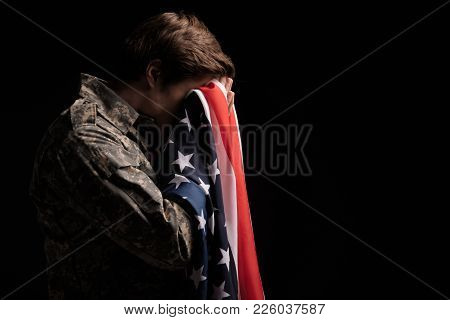 Despondent Military Man Covering His Face With Hands And Holding Usa Flag. Concept Of Despair. Isola