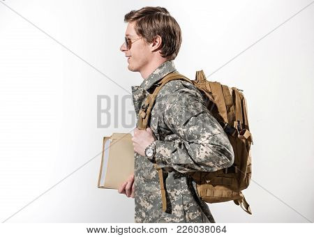 Happy Male Soldier Going Somewhere. He Is Smiling And Holding Document Case In Hand. Young Guy Weari