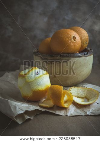 A Rustic Wooden Bowl Filled With Oranges.  One Orange Is Peeled And Sitting On Paper With The Peel.