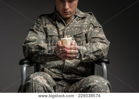 Serious Disabled Military Man Sitting In Wheelchair With Upset Look. He Is Having Candle In Hands An
