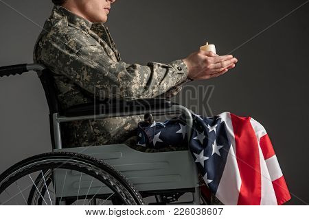 Disabled Male Soldier Sitting In Wheelchair. He Is Having Candle In Hands And Usa Flag On His Knees.