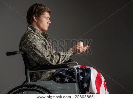 Unhappy Paralyzed Military Man Sitting In Invalid Chair With Serious Look. He Is Holding Suppository