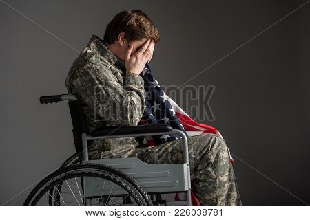 Despondent Handicapped Veteran Sitting In Invalid Chair. He Is Covering His Face With Hands And Hold