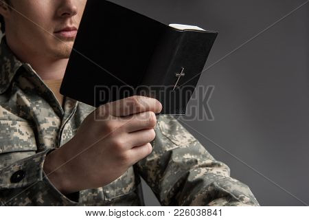 Male Soldier Holding The Bible In His Hand And Reading It. He Is Wearing Military Uniform. Isolated