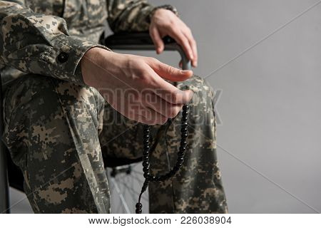 Close Up Of Male Hand Holding Beads. Man Is Sitting In Wheelchair And Wearing Military Uniform. Isol