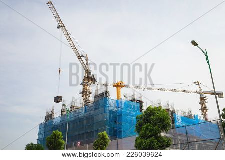 High Building Under Construction With Cranes Working