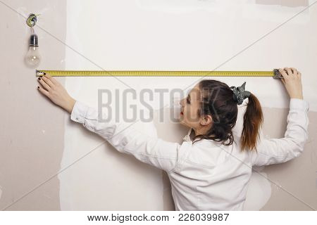 Woman With A Measure Tape Working In A Construction.
