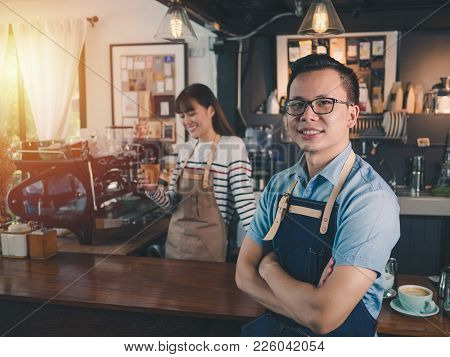 Asian Man Barista Wear Blue Apron Successful Small Business Owner Standing With Employee In Backgrou