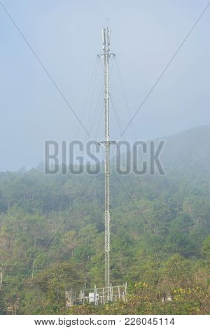 Metallic Broadcasting Tower On Mountain In Foggy Day In Asian