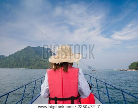 Women Wearing In Red Life Jackets Stand At Deck Of Ship And Look At Ocean.