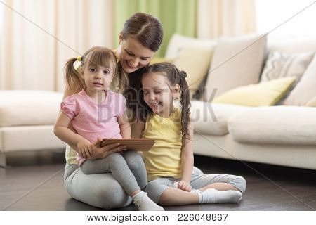 Cute Mom With Her 2 Years Old Little Daughter And 5 Years Old Daughter Playing With Digital Tablet A