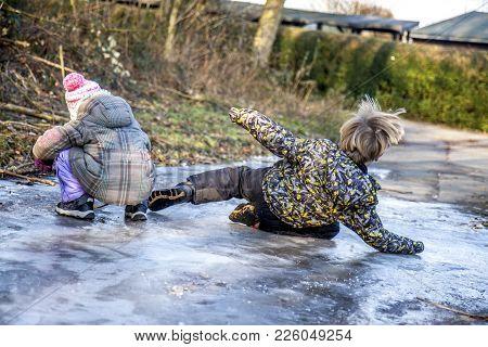 Little Boy Has A Side-slip On The Slippery Ice