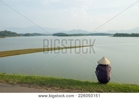 Landscape In Sunset With Land Strip Jutting Out To River. Vietnamese Farmer Sit Seeing The Scene. Co