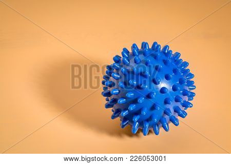 spiky rubber  ball roller for self massage, reflexology and myofascial release, beige background with a shadow