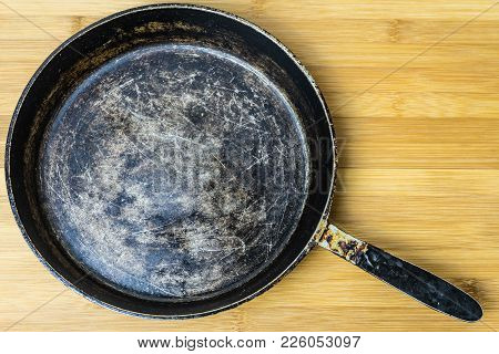 Old Frying Pan On A Bamboo Background. Photo Of An Old Pan.