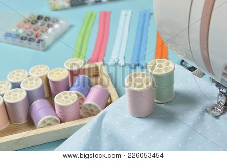 Fabrics On Sewing Machine Amid The Scissors, Shirt Buttons, Zipper, Pin And Colorful Thread Rolls Fo