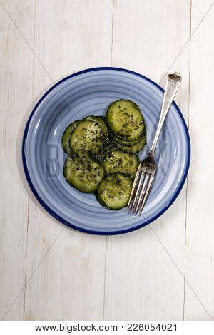 Cucumber Salad With Vinegar And Dried Parsley On A Blue Plate