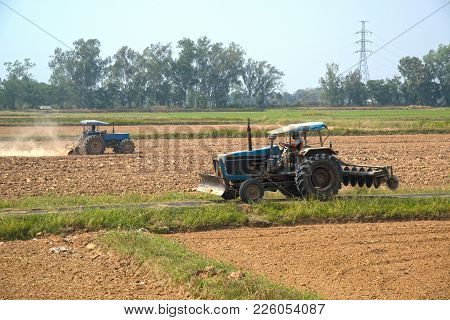 Surin,thailand-february 7 , 2018 : Unidentified Tractor Working In A Field Opening Preparing Soil Fo