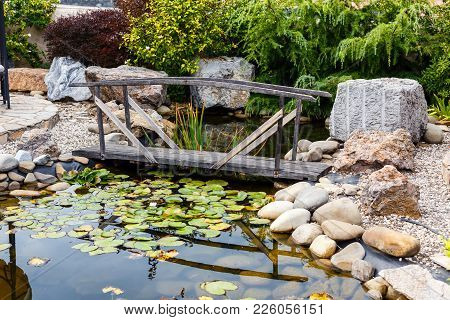 Vintage Wooden Bridge Over The Pond With Water Lilies In The City Park.