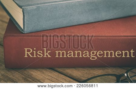 Risk Management Concept, Old Risk Analysis Textbooks, Antiquarian Books Pile On Wood Table.