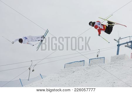 KRASNOE OZERO, LENINGRAD REGION, RUSSIA - FEBRUARY 1, 2018: Andrey Uglovski (red) of Russia and Oskar Elofsson of Sweden, compete in dual mogul during Freestyle Europa Cup competitions