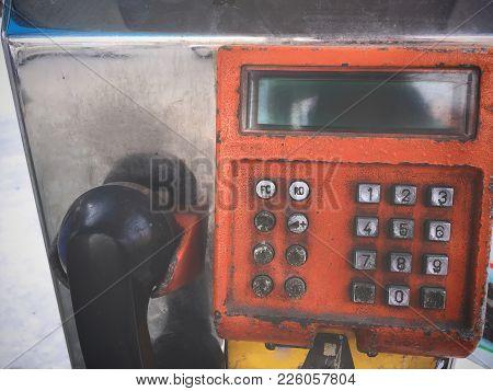 Close Up Old Grungy Orange Public Payphone