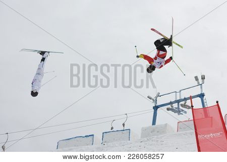 KRASNOE OZERO, LENINGRAD REGION, RUSSIA - FEBRUARY 1, 2018: Andrey Uglovski (red) of Russia and Oskar Elofsson of Sweden compete in dual mogul during Freestyle Europa Cup competitions