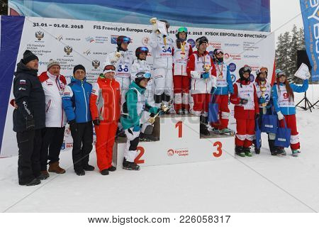 KRASNOE OZERO, LENINGRAD REGION, RUSSIA - FEBRUARY 1, 2018: All winners in dual mogul of Freestyle Europa Cup on the podium after award ceremony. Podium occupied by male and female athletes