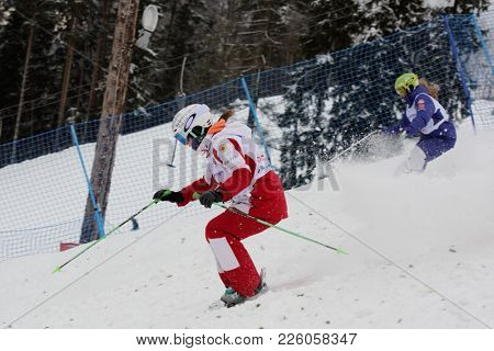 KRASNOE OZERO, LENINGRAD REGION, RUSSIA - FEBRUARY 1, 2018: Anastasiia Smirnova (red) and Marina Mishurina, both of Russia, compete in dual mogul during Freestyle Europa Cup competitions
