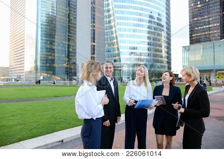 Employees Of Large Corporation Walking In   With Tablet, Laptop, Notebook And Document Case. Concept