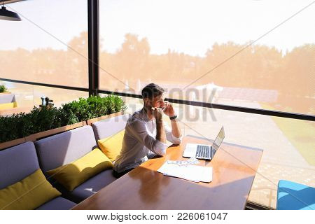 Caucasian Real Estate Broker Speaking By Smartphone With Customer And Using Laptop. Persistent Young