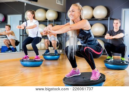 Dedicated And Cheerful Friends In Workout Team Doing Squats On Half Ball In A Fitness Gym Class. Cor