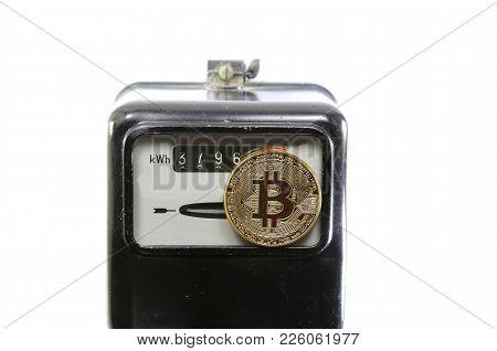 Big Golden Bitcoin Coin Over An Analog Electric Power Meter
