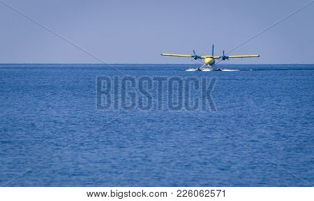 Private Seaplane Or Hydroplane Landing In The Ocean Lagoon In One Of The Maldives Islands.