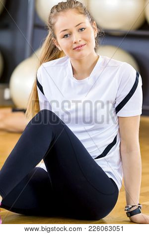 Smiling Young Woman Taking A Break From Training At The Fitness Gym. Workout Team Resting In The Bac