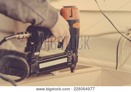 Man Builds Furniture In The Carpentry Shop. Toned Image.