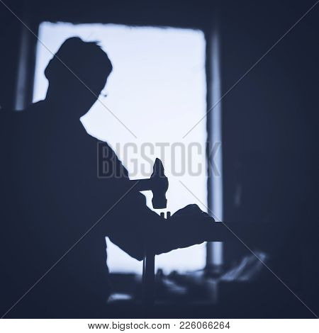 Silhouette Of A Carpenter Working With A Hammer Against A Window. Toned Image.