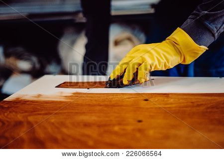 Carpenter Is Painting A Wood With Lacquer. Toned Image.