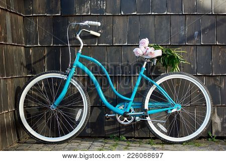 Shot Of A Blue City Bicycle Near The Wall With A Bunch Of Pink Peonies On The Seat Copyspace Flowers