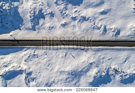 Desolate country road in icy conditions viewed from straight above
