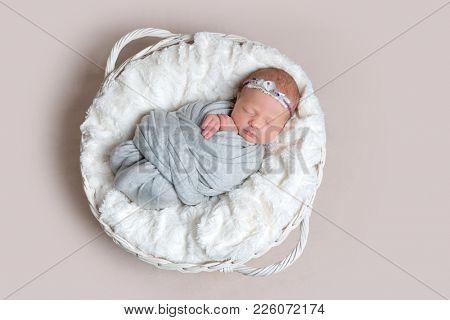 Newborn girl sleeps on white blanket, top view