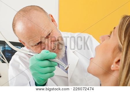 Mature Male Dentist Using Dental Drill On Female Patient - Dental Decay Treatment