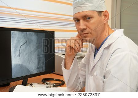Doctor in hospital at monitor with coronary angiography