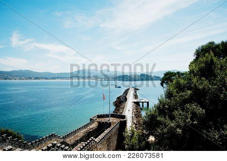Beautiful seascape with a pier in sunny day, view from the old castle wall in city Bayona, Galicia, Northen Spain